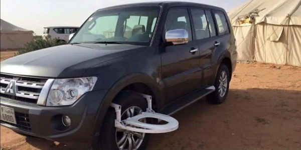 Mitsubishi SUV with toilet seat on the front wheel - cl